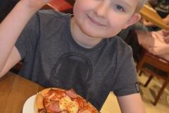 Mikołaj zaraz skosztuje pierwszy kawałek pizzy.
