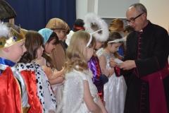Ksiądz Proboszcz rozdaje obrazki dzieciom.
