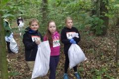 Uczniowie kl. 4 Mikołaj, Patrycja i Karolina podczas zbierania śmieci w parku.