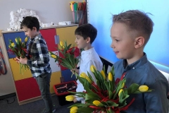 Szymon, Mateusz i Ignacy wręczają koleżankom kwiaty -Dzień Kobiet w kl. 2.