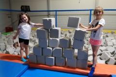Zuzia i Lenka z klasy pierwszej budują mur z kostek.